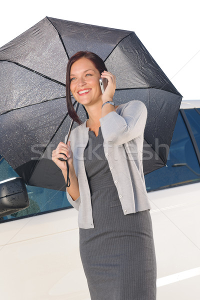 Businesswoman under umbrella by luxury car calling Stock photo © CandyboxPhoto