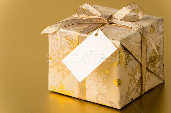 Christmas present with gold ribbon and blank tag Stock photo © CandyboxPhoto