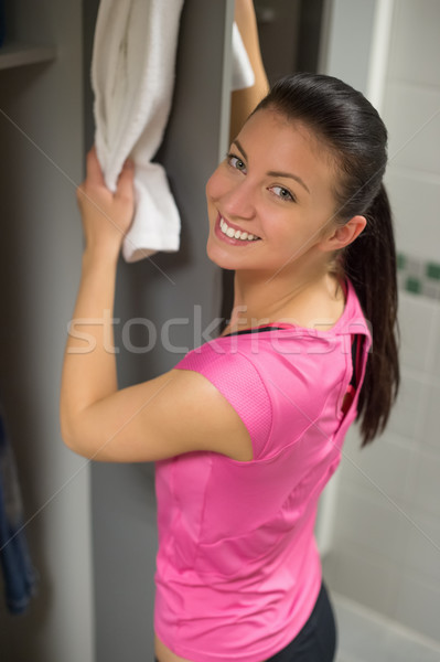 Woman placing towel on open locker door Stock photo © CandyboxPhoto