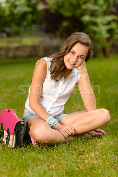 Smiling teenage girl sitting grass with satchel Stock photo © CandyboxPhoto