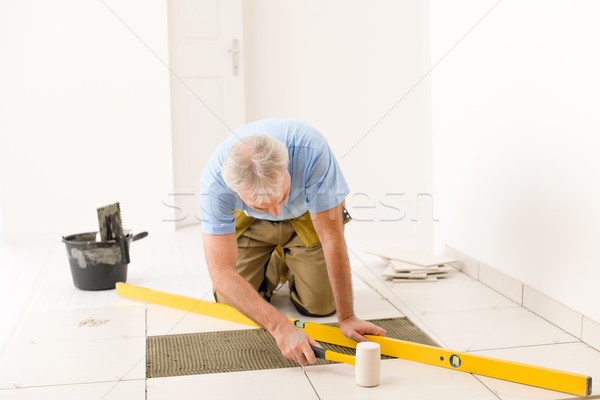 Home improvement, renovation - handyman laying ceramic tile  Stock photo © CandyboxPhoto
