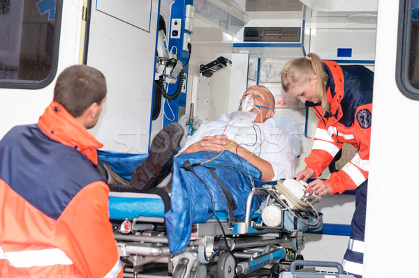 Paramedics putting patient in ambulance car aid Stock photo © CandyboxPhoto