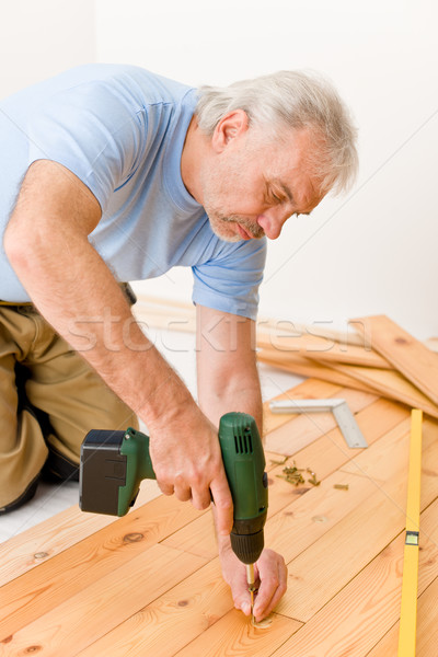 Stock photo: Home improvement - handyman installing wooden floor