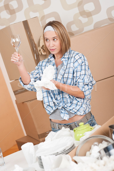 Moving house: Woman unpacking box with kitchen dishes Stock photo © CandyboxPhoto