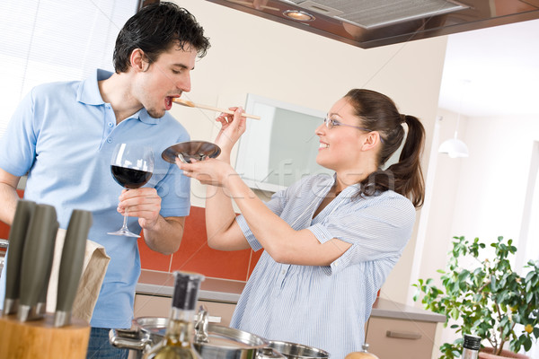 Happy couple cook in kitchen tasting food Stock photo © CandyboxPhoto