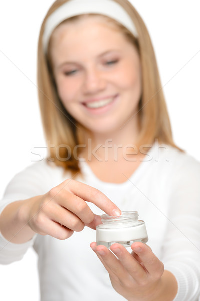 Smiling young girl applying moisturizer cream face Stock photo © CandyboxPhoto