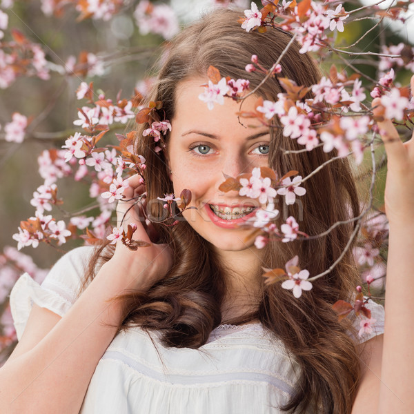 Girl with braces holding blossoming tree branch Stock photo © CandyboxPhoto