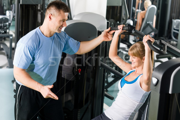 Young woman exercise on shoulder press machine Stock photo © CandyboxPhoto