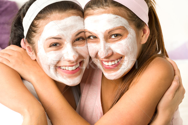 Blissful girls applying mask hugging each other Stock photo © CandyboxPhoto