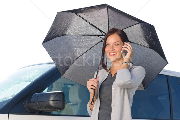 Businesswoman under umbrella by luxury car calling Stock photo © CandyboxPhoto