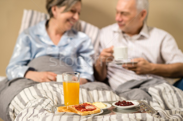 Stock photo: Pensioners drinking coffee in the bed