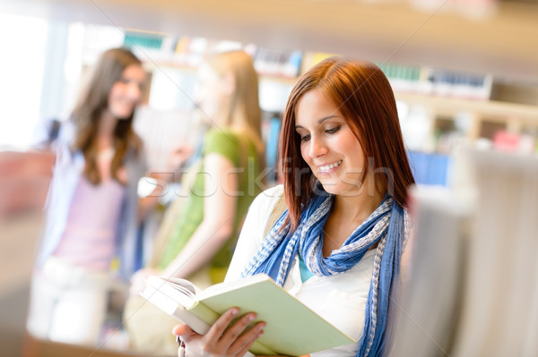 Teenage woman read among book shelves library Stock photo © CandyboxPhoto