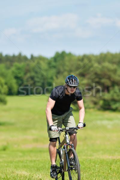 Sportive man mountain biking uphill sunny meadows Stock photo © CandyboxPhoto