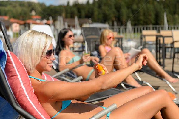 Jonge vrouwen ligstoel zonnebrandcrème bikini vrouwen Stockfoto © CandyboxPhoto