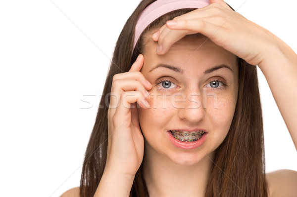 Worried girl with braces squeezing pimple isolated Stock photo © CandyboxPhoto
