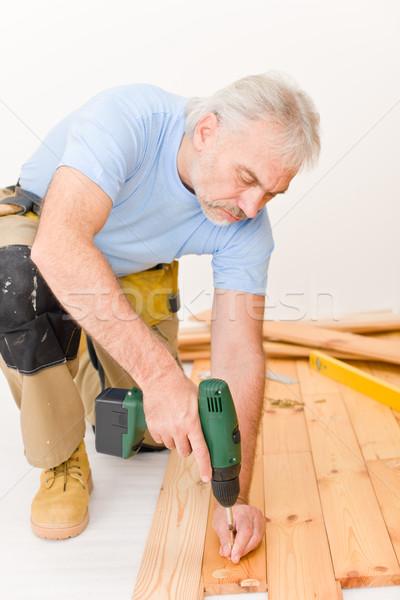 Stock photo: Home improvement - handyman installing wooden floor