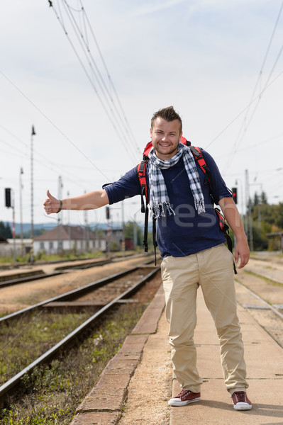 Man hitchhiking on railroad train station smiling Stock photo © CandyboxPhoto