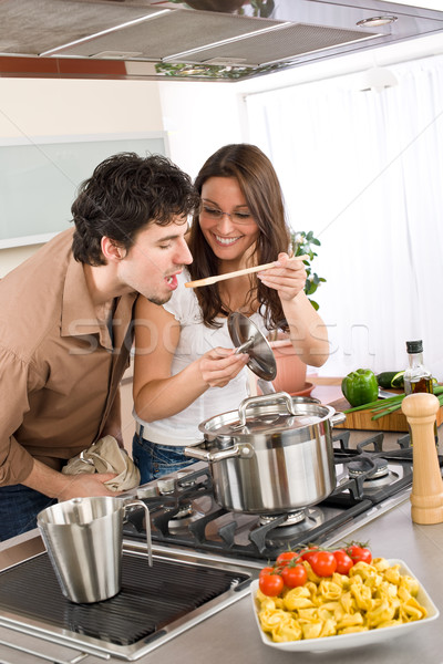 Couple cook in kitchen - man taste food Stock photo © CandyboxPhoto