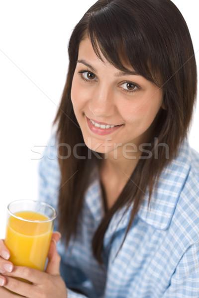 Stock photo: Smiling woman drink orange juice in pajamas