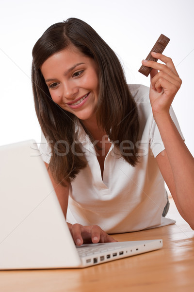 Happy teenager with laptop holding chocolate bar Stock photo © CandyboxPhoto