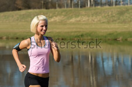 Young woman jogging by sunny river bank  Stock photo © CandyboxPhoto