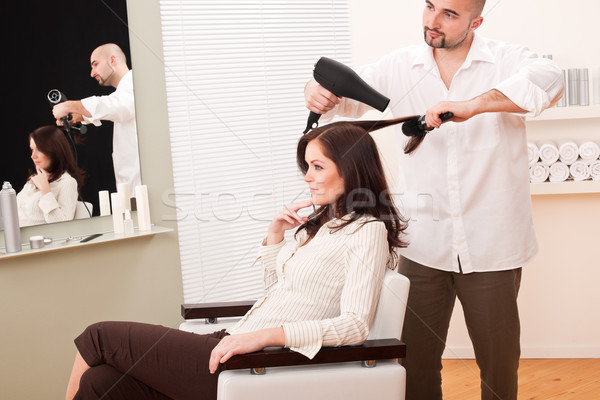 Stock photo: Professional hairdresser with hair dryer at salon with customer