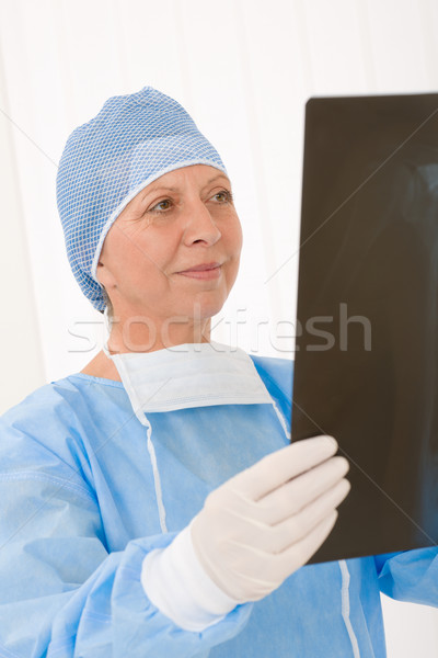 Stock photo: Senior surgeon female hold x-ray protective overall