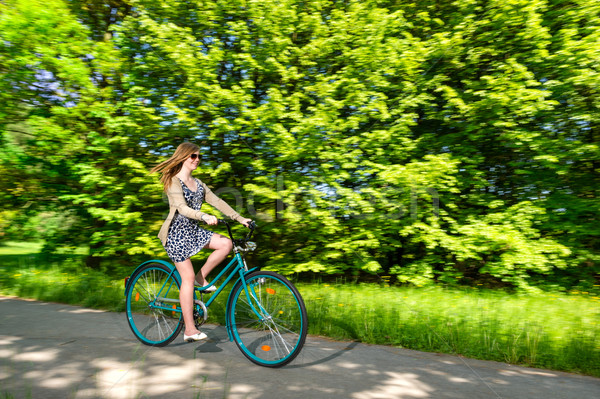 Young woman cycling during sunny summertime Stock photo © CandyboxPhoto