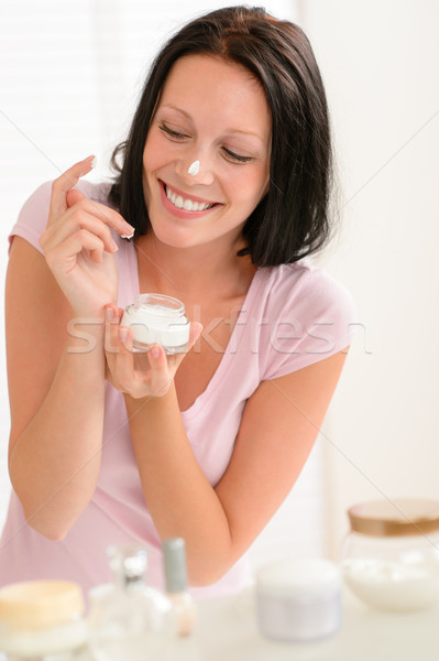 Smiling woman put moisturizer cream on nose Stock photo © CandyboxPhoto