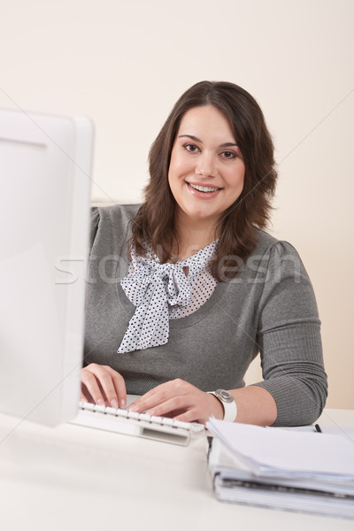 Stock photo: Happy businesswoman sitting at office desk