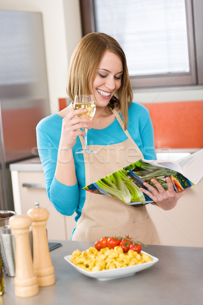 Cooking - Smiling woman reading recipe from cookbook Stock photo © CandyboxPhoto