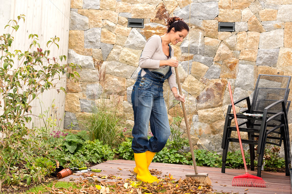 Young woman sweeping leaves veranda backyard happy Stock photo © CandyboxPhoto