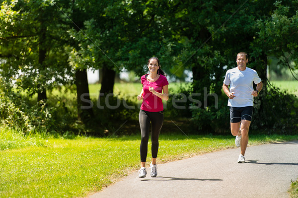 Boyfriend and girlfriend running a race outdoors Stock photo © CandyboxPhoto