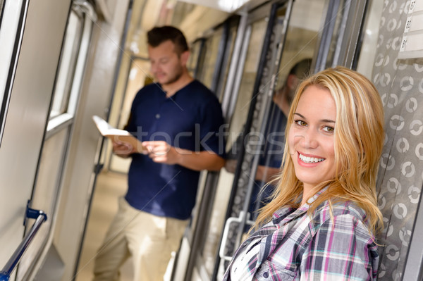 Stock photo: Woman smiling and man reading in train