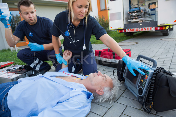 Paramedics checking pulse of unconscious man Stock photo © CandyboxPhoto