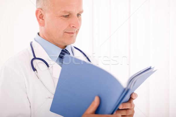 Stock photo: Mature doctor male look down in document
