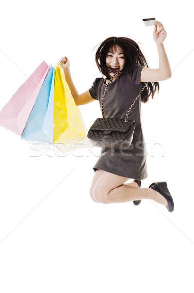 Jumping Chinese woman holding shopping bags and credit card. Stock photo © cardmaverick2