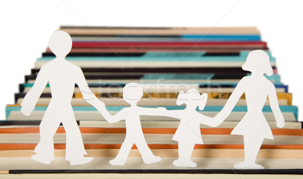 Stock photo: Family figures made from paper with books background