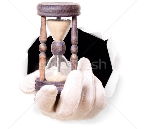 Man with gloves is holding sand clock in his finger through a hole Stock photo © carenas1
