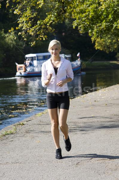 Futó aranyos fiatal lány fut park folyó Stock fotó © carlodapino