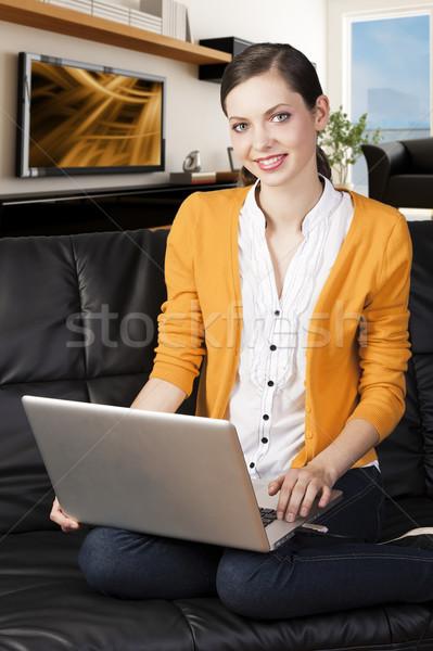 Lány kanapé laptop mosoly külső lencse Stock fotó © carlodapino