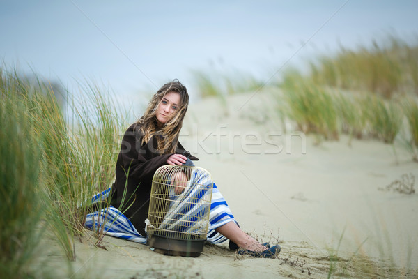 Beautiful girl with a birdcage in a dune Stock photo © castenoid