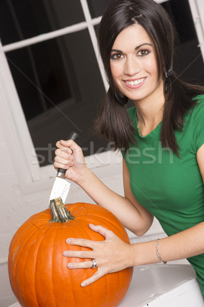 Excited Woman Cutting Carving Halloween Pumpkin Jack-O-Lantern Stock photo © cboswell