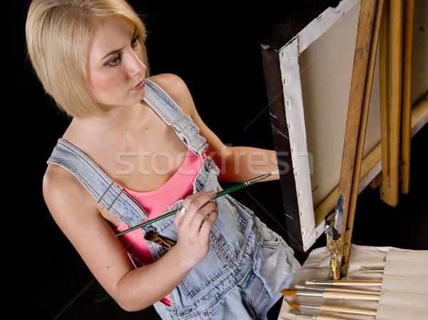 Happy Blond Woman Provides Finishing Touches to Painting on Ease Stock photo © cboswell