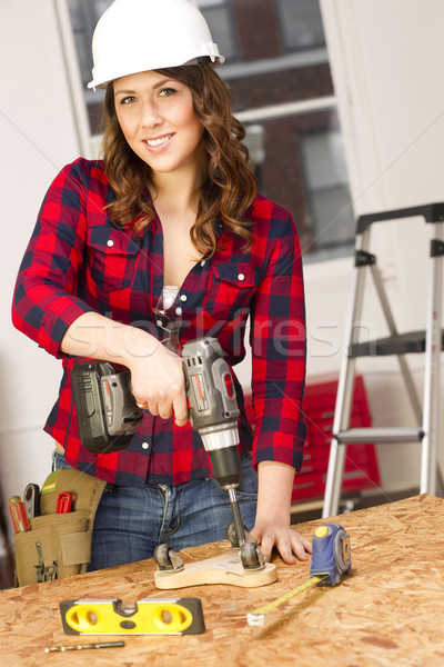 Stock photo: Woman Works on a Bench Repairing A Dolly