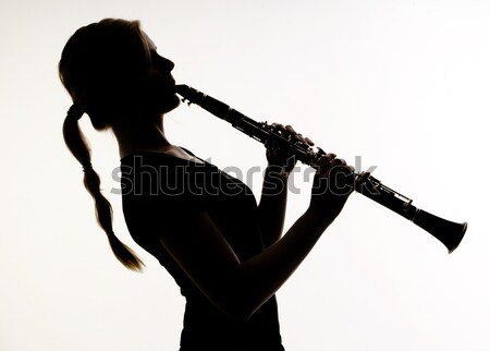 Female Musician in Silhouette Practices Woodwind Technique on Cl Stock photo © cboswell