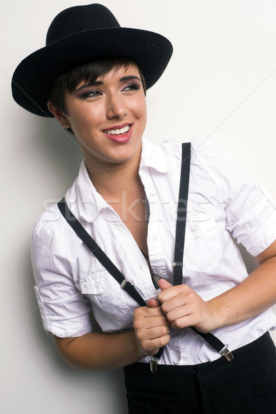 Young Androgynous Woman Stands Wearing Hat Suspenders White Back Stock photo © cboswell