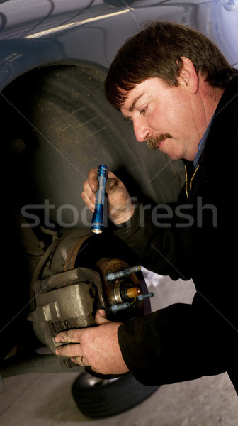 Auto Technician Mechanic Checks Rotors on Car Braking System Stock photo © cboswell