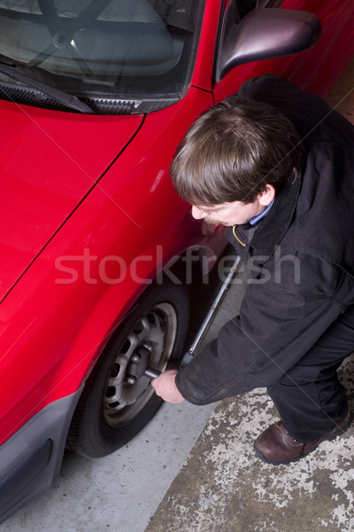 Auto Technician Uses Breaker Bar Loosening Lug Nuts on Car Stock photo © cboswell