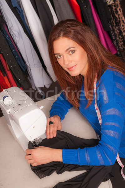 Woman Seamstress Works Making Reparing Clothes at Sewing Machine Stock photo © cboswell